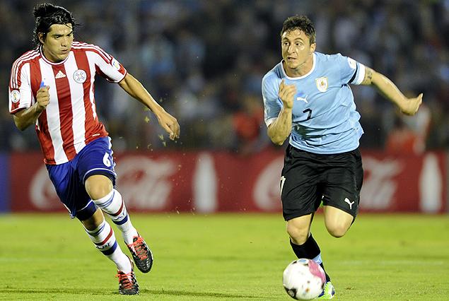 """""""Cebolla"""" Rodríguez avanza con el balón perseguido por el paraguayo Oviedo."""