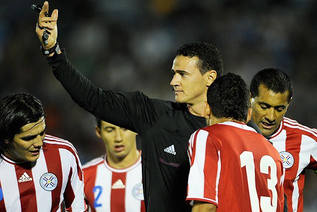 El árbitro colombiano Roldan rodeado de jugadores paraguayos. Pésimo fue su arbitraje.