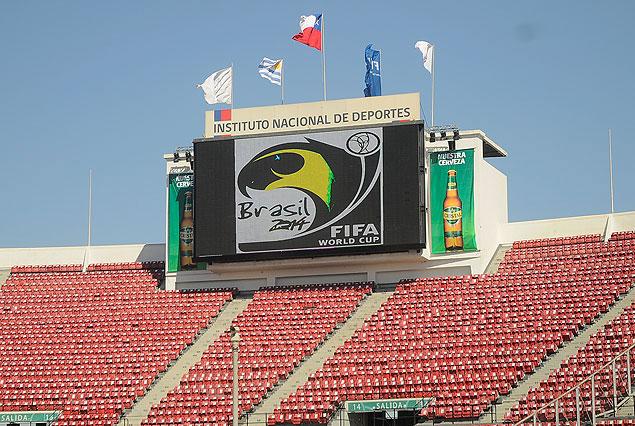 El placard del Estadio Nacional captado hace instantes. Ya está todo pronto para la fiesta. Las banderas de los países participantes, de la FIFA y el logo de Brasil 2014.