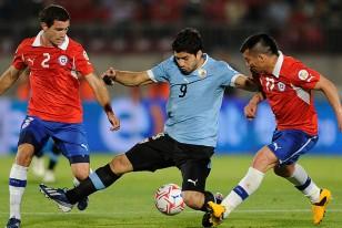 Luis Suárez intenta dominar el balón, ante la marca de los chilenos Eugenio Mena y Gary Medal en su marcha.