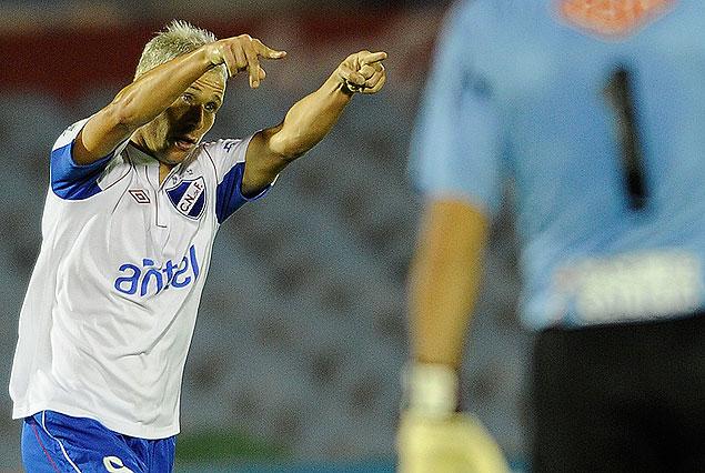Israel Damonte dedica su golazo, el primero de Nacional. Damián Frascarelli lo sufre en primer plano.