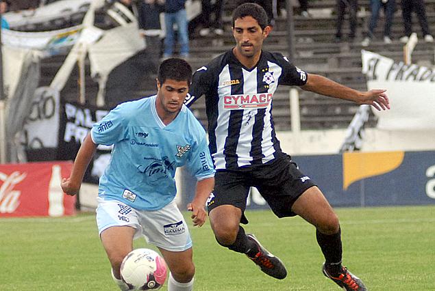 Simón Pagua escapa a la marca de Hernán Menosse.