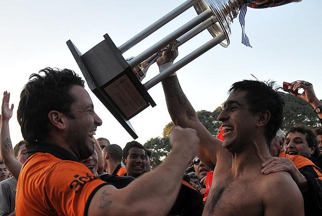Maureen Franco, con el torso desnudo, levanta la Copa de Campeón.