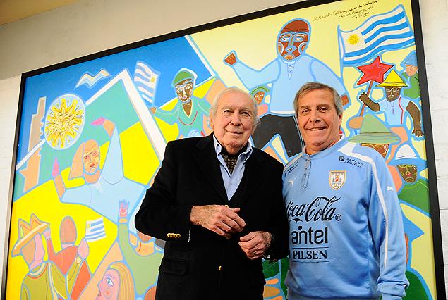 Oscar Tabárez y Carlos Páez Vilaró posan junto al mural que desde hoy pone una nota de color y alegría en el gran salón comedor del Complejo Celeste.