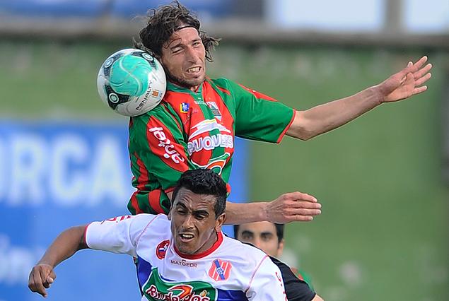 El zaguero rojiverde Rodrigo Canosa con alto vuelo en el Olímpico como en la imagen sobre Wanderson Silveira.