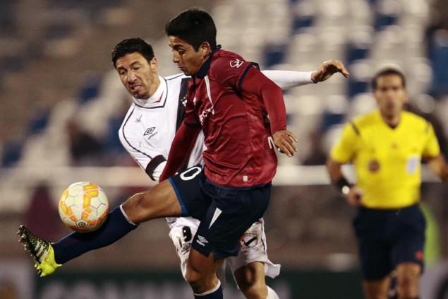 El defensor chileno Fabián Manzano (despeja el balón ante la amenazante presencia de Juan Manuel Olivera.