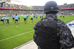 Los titulares uruguayos corren por la cancha, bajo la atenta mirada de un soldado boliviano.
