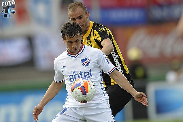 Sebastián Fernández cubriendo la pelota frente a la marca de Carlos Valdez.