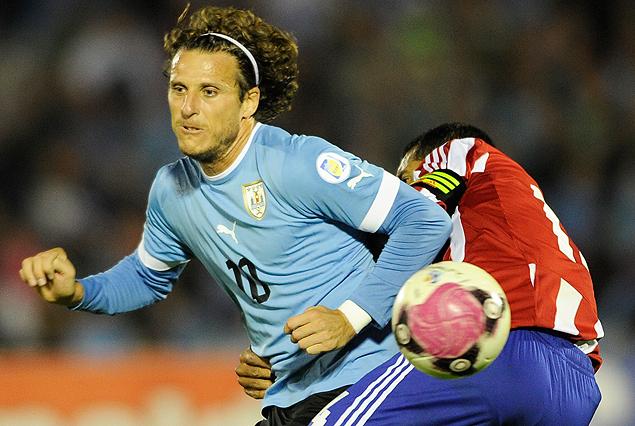 Diego Forlán forceja con el paraguayo Paulo Da Silva, le pelota sigue de largo.