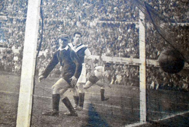 """La Tribuna Olímpica repleta. Uruguay se despide de Montevideo ante un equipo alemán. Gana 5:1. En la fotografía la pelota está en las mallas, el golero y el jugador alemán miran. Atrás """"Lucho"""" sale corriendo a festejar su primer gol con la celeste en el pecho el día del debut."""